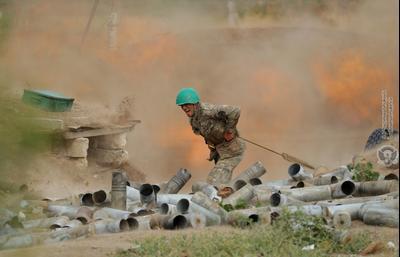 Армянин стреляет из артиллерийского орудия во время боя с азербайджанскими войсками в Нагорном Карабахе, сентябрь 2020 г.